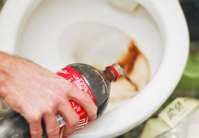 Pouring the Coke around the rim of the water-closet